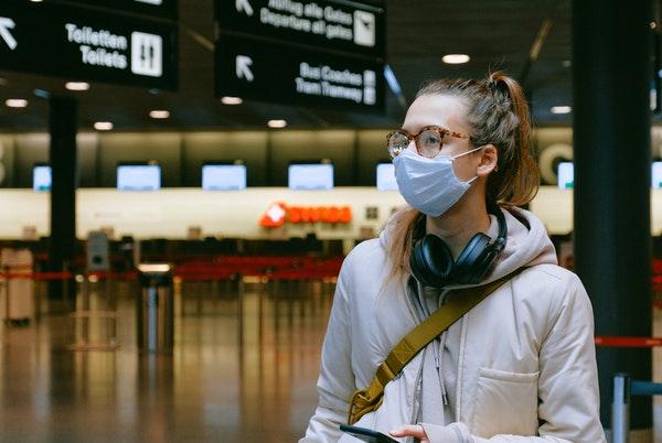 空港でマスクをする女性