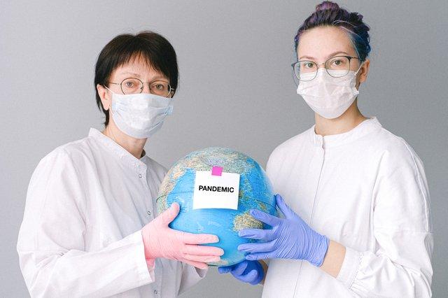 地球儀を掲げるマスク姿の女性二人