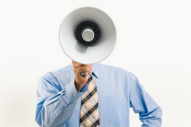 拡声機で伝える男性