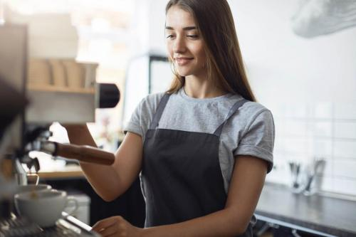 Female student on her summer job serving coffee working as a barista in a local pastry shop