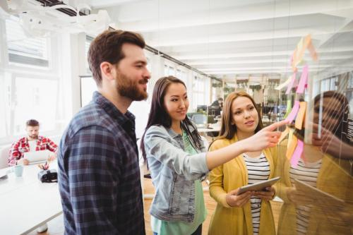 Coworkers looking at sticky notes pointed by female photo editor